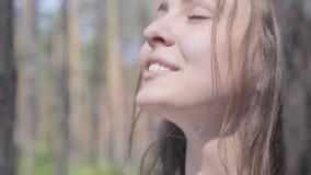 Close-upportret van het gelukkige het glimlachen jonge vrouw kijken rond in pijnboom bosconcept het kamperen Vrije tijd en reis a stock footage