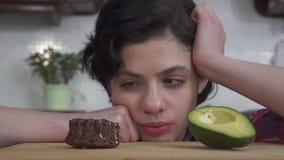 Close-upportret van het hongerige mooie meisje kiezen tussen weinig smakelijke brownie cupcake met het heerlijke berijpen en stock videobeelden