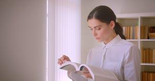 Close-upportret van het jonge aantrekkelijke Kaukasische boek die van de studentenlezing zich in bibliotheek met boekenrekken op  stock footage