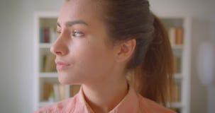 Close-upportret van het jonge aantrekkelijke vrouwelijke student draaien en het bekijken camera die gelukkig in de universiteitsb stock videobeelden
