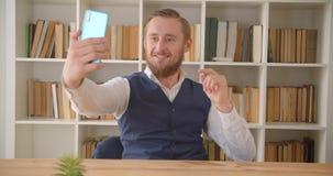 Close-upportret van het jonge Kaukasische businessmantaking selfies op de telefoon op de werkplaats binnen met boekenrekken  stock videobeelden