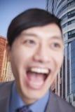 Close-upportret van het jonge mens lachen, nadruk op achtergrond van de bouw van buitenkanten en wolkenkrabbers stock foto