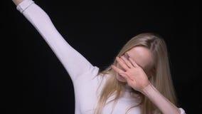 Close-upportret van het jonge mooie blonde vrouwelijke betten met vertrouwen die camera met geïsoleerde achtergrond bekijken stock video