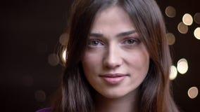 Close-upportret van het jonge mooie Kaukasische meisje glimlachen en het bekijken recht camera met plezier stock video