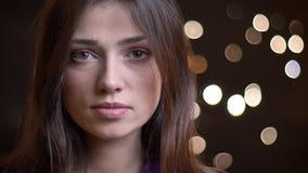 Close-upportret van het jonge vrij Kaukasische meisje recht bekijken camera met nachtlichten op de achtergrond stock videobeelden