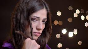Close-upportret van het jonge vrij Kaukasische vrouwelijke spelen met haar haar en seductively het bekijken recht camera stock video