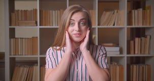 Close-upportret van het jonge vrij Kaukasische vrouwelijke student glimlachen met opwinding die camera in de universiteit bekijke stock videobeelden