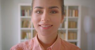 Close-upportret van het jonge vrij vrouwelijke student draaien en het bekijken camera die cheerfully in de universiteitsbibliothe stock footage