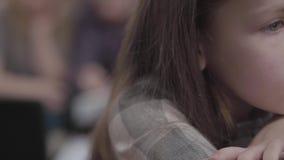 Close-upportret van het kleine droevige meisje met lange haarzitting op de stoel in de voorgrond De bezige moeder en stock footage