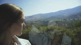 Close-upportret van het meisje die door het busvenster kijken op het landschap stock videobeelden