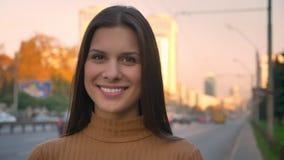 Close-upportret van het mooie donkerbruine meisje letten op in camera met bescheiden glimlach op wegachtergrond stock video
