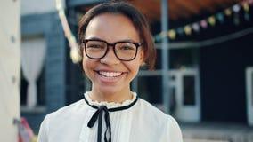 Close-upportret van het mooie gemengde rasmeisje lachen in openlucht in stadsstraat stock videobeelden