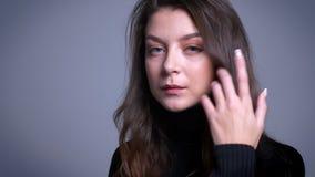 Close-upportret van het overweldigen van jong vrouwelijk model die haar haar achter het oor plooien en voor de camera stellen stock video
