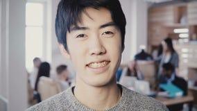 Close-upportret van het succesvolle Aziatische mannelijke creatieve manager glimlachen op modern kantoor Knappe mens die camera 4 stock video
