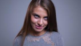 Close-upportret van het verleidelijke jonge Kaukasische vrouwelijke glimlachen knipogend en bekijkend camera stock footage