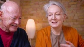 Close-upportret van hogere grijs-haired Kaukasische echtgenoten die met elkaar spreken die blij en gelukkig zijn stock footage