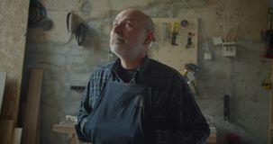 Close-upportret van hogere mannelijke timmerwerk hoofd status bij het houten vervaardiging letten op in camera die ernstig zijn e stock footage