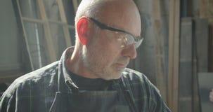 Close-upportret van hogere timmerman in veiligheidsbril die het proces controleren bij houten fabriekshorloges in camera stock videobeelden