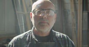 Close-upportret van hogere timmerwerkmeester in veiligheidsbril die bij houten fabriekshorloges in camera werken die ernstig zijn stock footage