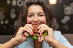 Close-upportret van hongerige jonge Kaukasische vrouw, beetsandwich royalty-vrije stock fotografie
