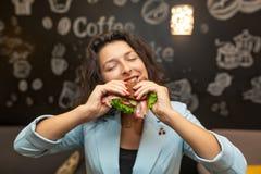 Close-upportret van hongerige jonge Kaukasische vrouw, beetsandwich stock fotografie