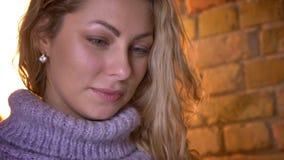 Close-upportret van jong aantrekkelijk blonde Kaukasisch wijfje die aan camera draaien en cheerfully in comfortabel glimlachen stock video