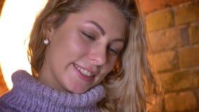 Close-upportret van jong aantrekkelijk blonde Kaukasisch wijfje die aan camera draaien en met schuchterheid in comfortabel glimla stock footage
