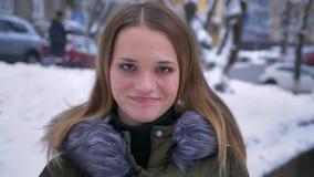Close-upportret van jong aantrekkelijk donkerbruin caucasainwijfje die cheerfully en camera in een de winterdag glimlachen bekijk stock videobeelden