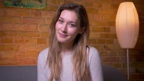 Close-upportret van jong aantrekkelijk Kaukasisch donkerbruin wijfje die camera bekijken en cheerfully het situeren op glimlachen stock footage