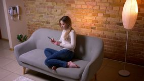 Close-upportret van jong aantrekkelijk Kaukasisch donkerbruin wijfje die de telefoon texting die op de bank binnen in comfortabel stock footage