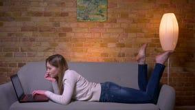 Close-upportret van jong aantrekkelijk Kaukasisch donkerbruin wijfje die online op laptop bestuderen en op de laag liggen stock video