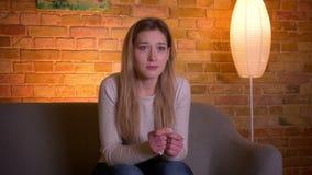 Close-upportret van jong aantrekkelijk Kaukasisch donkerbruin wijfje die op een droevige film op TV letten en het situeren op de  stock footage