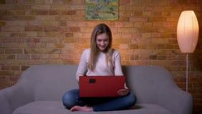Close-upportret van jong aantrekkelijk Kaukasisch donkerbruin wijfje die op een grappige film op laptop en het lachen letten stock videobeelden