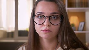 Close-upportret van jong aantrekkelijk Kaukasisch wijfje die in glazen camera binnen in flat bekijken stock video