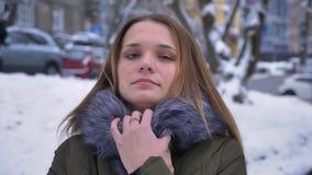 Close-upportret van jong aantrekkelijk Kaukasisch wijfje met donkerbruin haar die en in een comfortabele de winterlaag bevriezen  stock footage