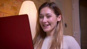 Close-upportret van jong aantrekkelijk leuk donkerbruin op een film op laptop letten en wijfje die en blij worden geamuseerd stock videobeelden