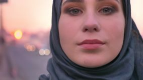 Close-upportret van jong aantrekkelijk moslimwijfje die in hijabgezicht vol vertrouwen camera met stedelijke stad op bekijken stock video