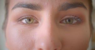 Close-upportret van jong aantrekkelijk vrouwelijk gezicht met ogen die camera bekijken stock video
