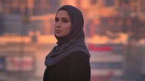 Close-upportret van jong aantrekkelijk wijfje die in hijab recht camera vol vertrouwen met stad op de achtergrond bekijken stock video