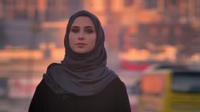 Close-upportret van jong aantrekkelijk wijfje die in hijab vol vertrouwen camera met de avondstad bekijken op stock video