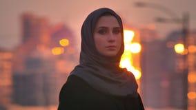 Close-upportret van jong charmant moslimwijfje die in hijab recht de stedelijke stad van de camera wuith avond op bekijken stock footage