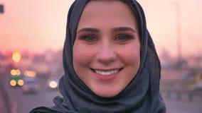 Close-upportret van jong charmant mousselinewijfje in hijab die gelukkig en recht camera glimlachen bekijken stock videobeelden