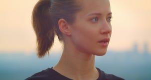 Close-upportret van jong gemotiveerd sportief wijfje jogger in een zwarte t-shirt die de mooie zonsondergang in openlucht bekijke stock video