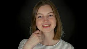 Close-upportret van jong glimlachend langharig Kaukasisch meisje in zwarte studio stock videobeelden