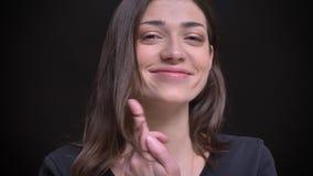 Close-upportret van jong Kaukasisch langharig donkerbruin meisje die flirtingly in camera op zwarte achtergrond glimlachen stock video