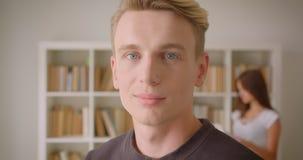 Close-upportret van jong Kaukasisch mannetje dat camera bekijkt die gelukkig status in de bibliotheek met een jong wijfje glimlac stock videobeelden