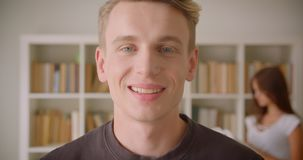 Close-upportret van jong Kaukasisch mannetje die camera bekijken die cheerfully status in de bibliotheek met jongelui glimlachen stock video