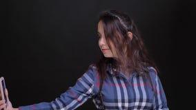 Close-upportret van jong Kaukasisch wijfje die selfies op de telefoon met de achtergrond nemen die op zwarte wordt geïsoleerd stock footage