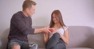Close-upportret van jong leuk Kaukasisch paar binnen in de flat Wijfje die de telefoonzitting op de laag gebruiken stock videobeelden