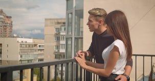 Close-upportret van jong leuk Kaukasisch paar dat mooie mening bekijkt die zich op het balkon van hun huis bevindt stock videobeelden